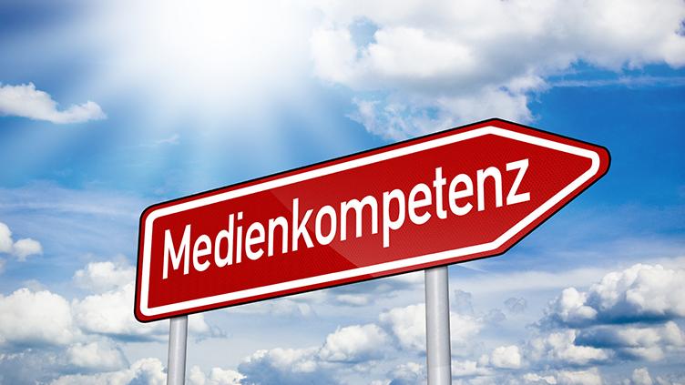 Das Titelbild zeigt ein Schild auf dem Medienkompetenz steht. Das Schild zeigt nach rechts die Richtung an.