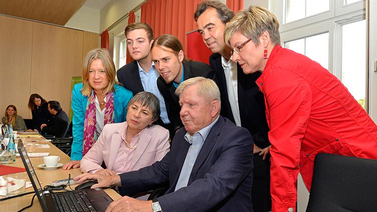 Eine Gruppe von Menschen schaut interessiert auf einen Laptop