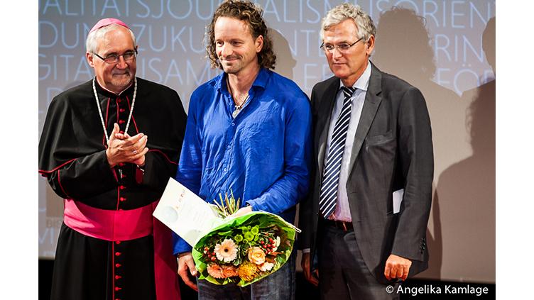 Drei Menschen, einer mit Blumenstrauß: Bischof Fürst; Preisträger Marc Wiese; Laudator Peter Frey (Katholischer Medienpreis 2014)