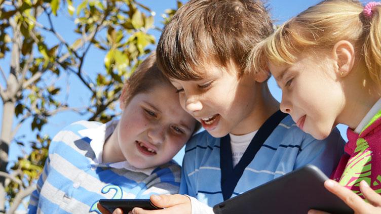 Drei Kinder schauen auf ein Smartphone, welches das mittlere Kind in den Händen hält.