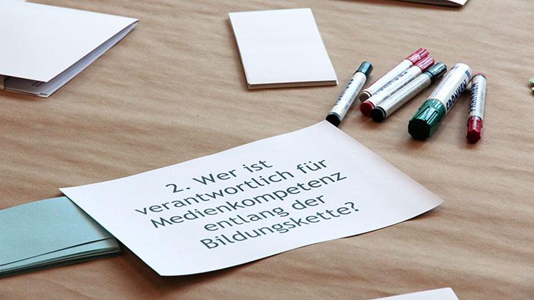 """Moderationskarte mit der Frage """"Wer ist verantwortlich für Medienkompetenz entlang der Bildungskette?"""" und Stifte beim World Café zum Thema Medienkompetenzvermittlung"""