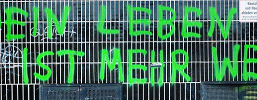 """Graffiti """"Dein Leben ist mehr wert"""" über einem Sperrmüll-Sofa; Symbolbild für das Thema Werte am Deutschen Katholikentag"""