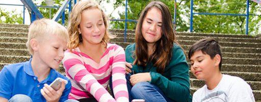 Kinder mit Smartphones (Symbolbild für das Thema Identität vor dem Hintergrund von Social Media)