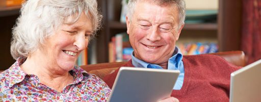 Ältere Frau und älterer Mann (Silver Surfer) am Tablet