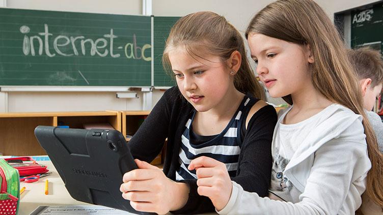 """Zwei Kinder schauen auf ein Tablet im Hintergrund ist eine Tafel zu sehen auf der """"internet-abc"""" geschrieben steht. - Kinder im Netz - aber sicher!"""