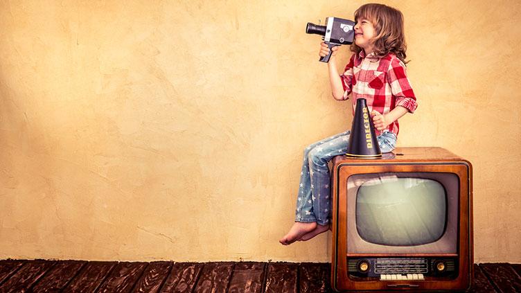Kind auf Fernseher mit Kamera; Symbolbild für aktive Medienarbeit