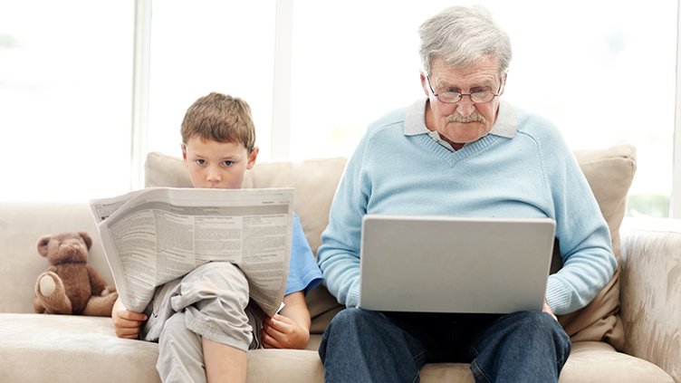 Junge liest Zeitung und sein Opa sitzt neben ihm vor dem Laptop