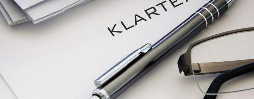 """Kugelschreiber, Brille auf Papier, auf dem das Wort """"Klartext"""" steht (Symbolbild für das Tagungsthema Journalismus der Zukunft)"""