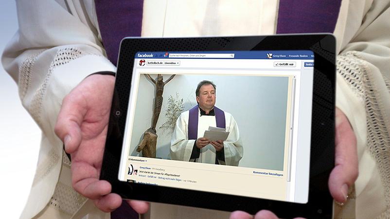 Pfarrer hält Tablet in seinen Händen. (Gottesdienste auch online)