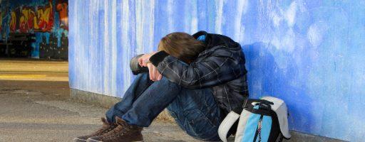 Zu sehen ist ein Jugendlicher, der vor einer Wand sitzt und seinen Kopf auf die Beine gelegt hat. Er sitzt in verschlossener Haltung da. - Auch digital ist brutal!