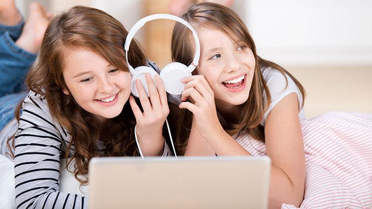 Zwei Mädchen liegen auf dem Bett vor einem Laptop und hören Musik - Zu viel ist ungesund