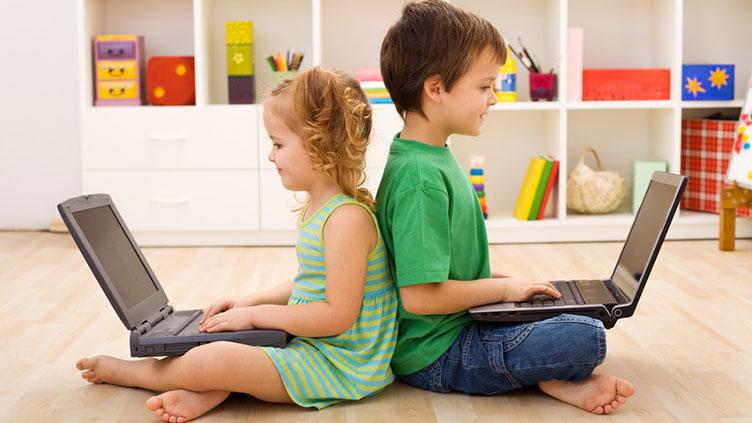 Mädchen und Junge vor dem Laptop