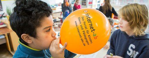 Kinder mit einem Luftballon mit der Aufschrift Internet-ABC
