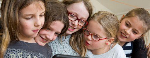 Eine Gruppe junger Mädchen sehen sich etwas auf einem Tablet an.