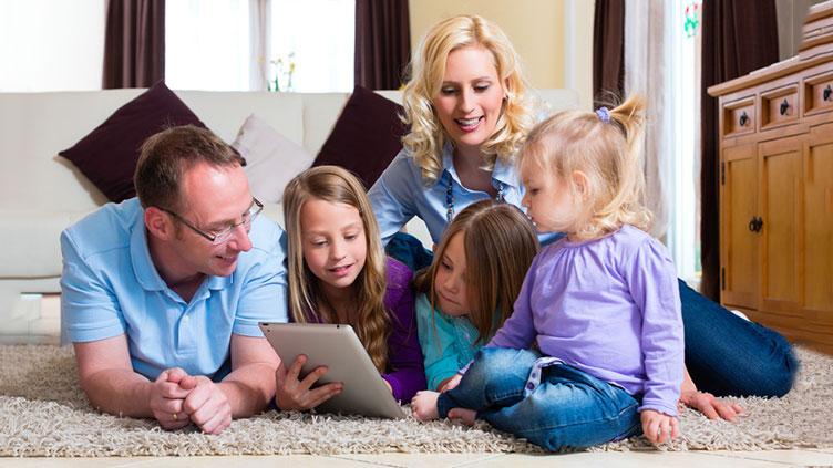 eine Familie sitzt auf dem Boden und schauen gemeinsam auf einen Tablet