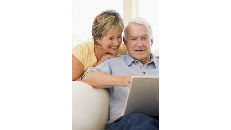 ein älteres Ehepaar sitzen zusammen vor einem Laptop