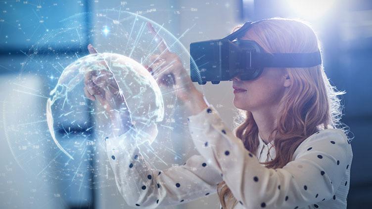 Frau mit VR-Brille zeigt mit dem Finger auf einen digitalen Globus