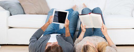 Mann liest ein E-Book und eine Frau liest ein Buch (Symbolild für E-Books in der Büchereiarbeit)
