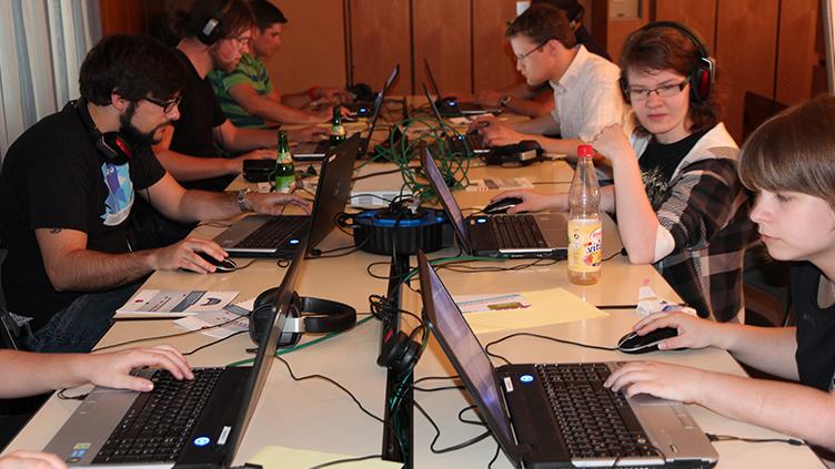 Eine Gruppe Jugendlicher sitzt sich am Tisch gegenüber. JedeR hat einen Laptop vor sich.