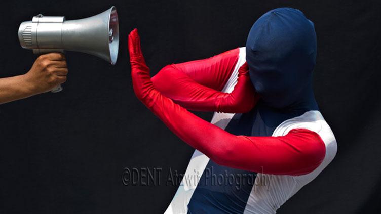 Ein Mann hält ein Megaphon in die linke Bildhälfte. Ein anderer Mann hält sich die Ohren zu und eine Hand entgegen das Megaphon