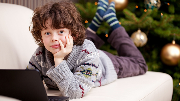 Kind liegt auf dem Sofa vor Laptop (Symbolbild für das Thema Computerspiele)