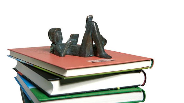 aufeinander gestapelte Bücher und darauf eine Figur
