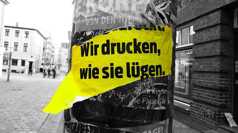 """Plakat-Ausriss """"Wir drücken, wie sie lügen"""""""
