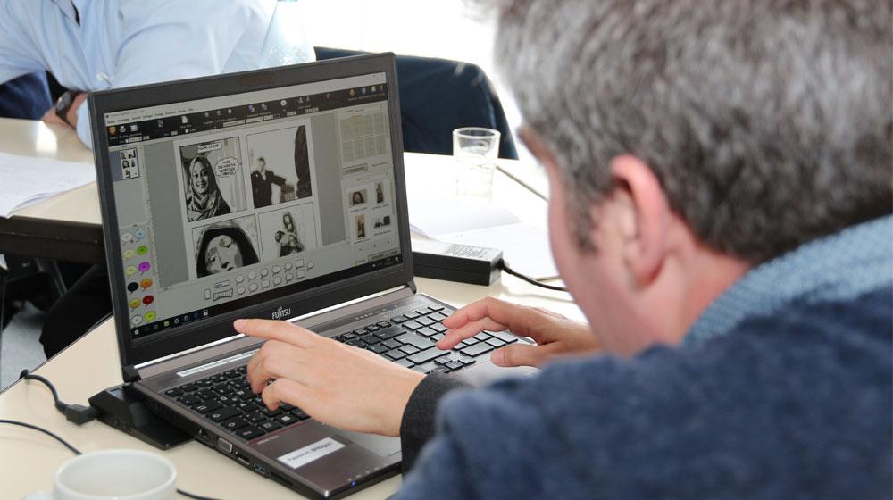Menschen vor einem Laptop mit einem Comic darauf zu sehen (Digital 2020)