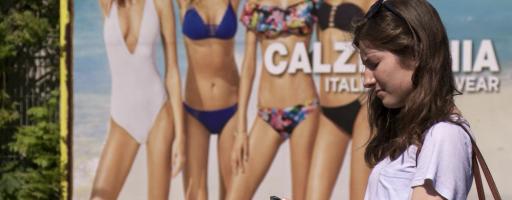 Selbstoptimierung - Anna, die Hauptfigur in der Dokumentation steht vor einer Werbetafel, welche Frauen in makelloser Bikini-Figur zeigt.