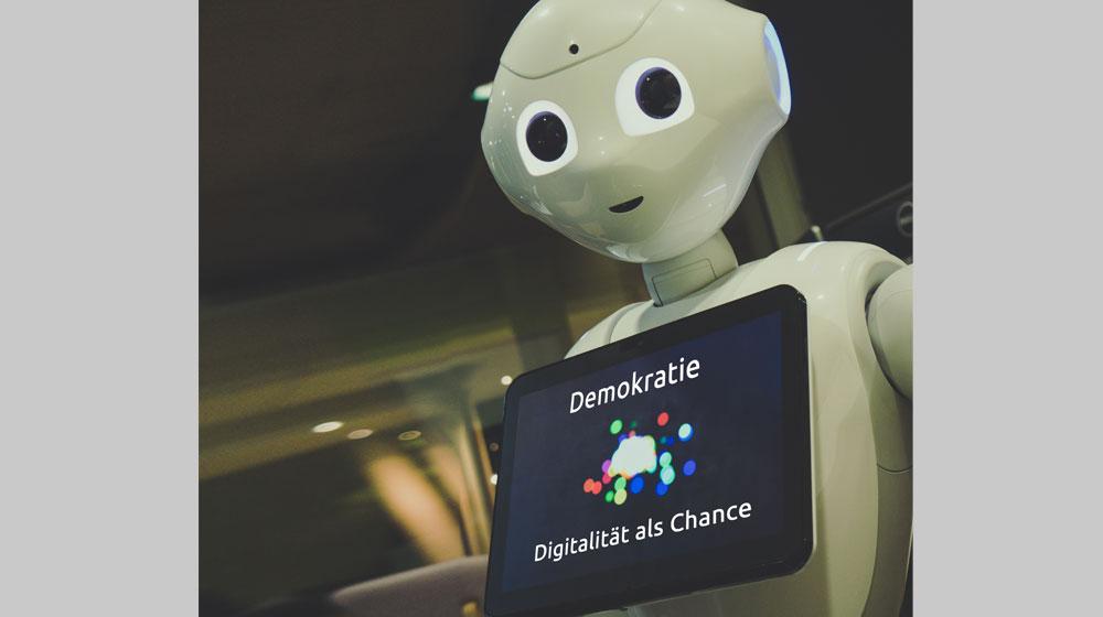 """Roboter mit Tablet, auf dem """"Demokratie. Digitalität als Chance"""" steht"""