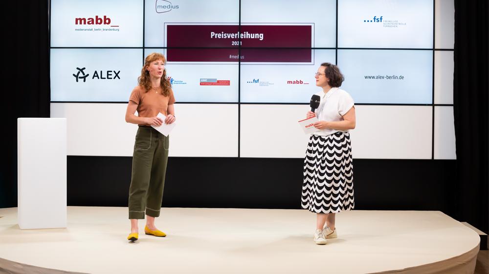 Zwei Menschen auf einer Bühne (Preisverleihung medius 2021)